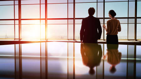 windows: equipo de personas de negocios con éxito. dos empresarios descansando y hablando en la oficina. hombre y mujer mirar la ciudad desde la ventana del centro de negocios.