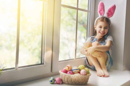 Buona Pasqua! Cute bambina bambino che indossa le orecchie di coniglio nel giorno di Pasqua. Ragazza seduta sulla finestra con un cesto di uova di Pasqua. Ragazza del bambino ride e gode di primavera e una vacanza.