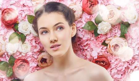 nude girl pretty young: Beautiful young woman on a background of pink flowers. The concept of beauty and health. Beautiful fashion bride, sweet and sensual. Stock Photo
