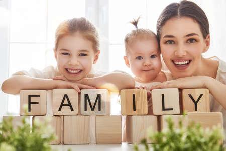 mignonne petite fille: Bonne famille aimante jouant avec des blocs et avoir du plaisir. Les blocs ont des lettres. M�re et ses filles exposent cubes et mot famille.
