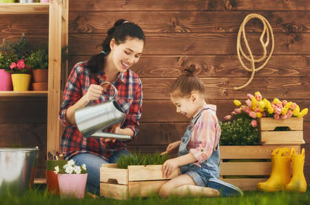Cute child girl helps her mother to care for plants. Mother and her daughter engaged in gardening in the backyard. Spring concept, nature and care.