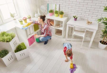 Familia feliz que limpia la habitación. Madre e hija hacen la limpieza de la casa. Una mujer joven y un poco de polvo niñas.