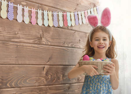laughing girl: Cute little child girl wearing bunny ears on Easter day. Girl holding basket with painted eggs. Stock Photo