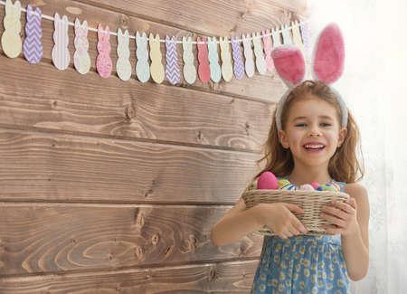 mignonne petite fille: La petite fille mignonne des enfants portant des oreilles de lapin le jour de P�ques. Girl holding panier avec des oeufs peints. Banque d'images