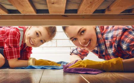 case colorate: Famiglia felice che pulisce la stanza. Madre e figlia fanno la pulizia della casa. Una giovane donna e una bambina bambino spazzato il pavimento.