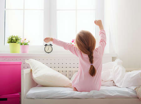 sunlight: A nice child girl enjoys sunny morning. Good morning at home. Child girl wakes up from sleep.