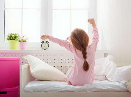 dobr�: Pěkný dítě dívka má slunečného rána. Dobré ráno doma. Dítě dívka se probudí ze spánku. Reklamní fotografie