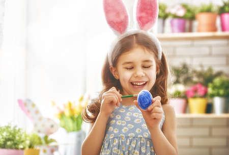 Frohe Ostern! Ein schönes Kind Mädchen Malerei Ostereier. Glückliche Familie für Ostern vorbereitet. Nettes kleines Kind Mädchen mit Hasenohren auf Ostern Tag. Standard-Bild