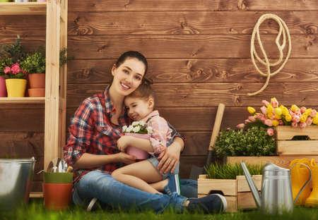 mignonne petite fille: Cute girl enfant aide sa m�re aux soins pour les plantes. M�re et sa fille engag�s dans le jardinage dans l'arri�re-cour. concept de printemps, la nature et les soins.