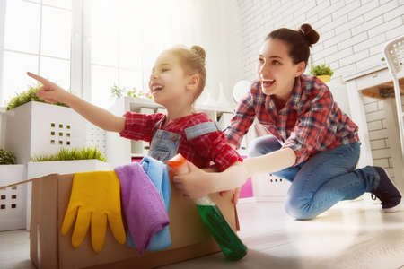 madre trabajando: Familia feliz que limpia la habitaci�n. Madre e hija hacen la limpieza de la casa. Una mujer joven y una ni�a peque�a que se divierten y montar en cajas de cart�n en su casa.
