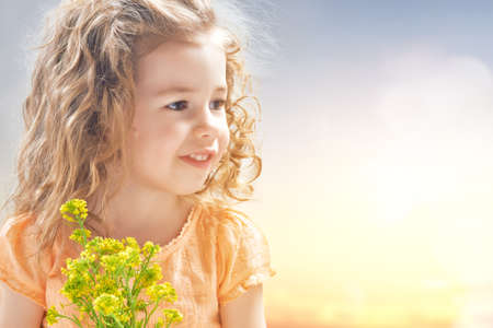 Cute child girl with flowers. Mothers day, spring concept.