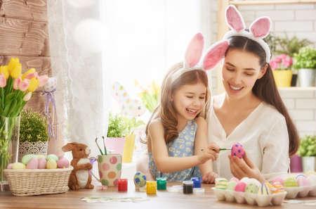 Gelukkig Pasen! Een moeder en haar dochter schilderij paaseieren. Gelukkige familie voorbereiding voor Pasen. Leuk weinig kind meisje draagt bunny oren op Pasen dag. Stockfoto