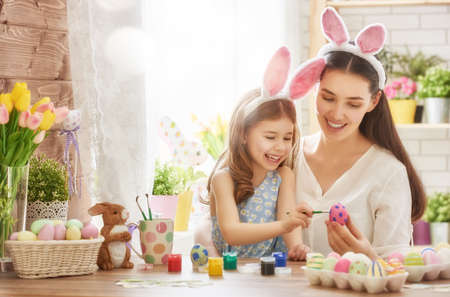 Happy easter! A mother and her daughter painting Easter eggs. Happy family preparing for Easter. Cute little child girl wearing bunny ears on Easter day. Stock Photo - 52913443