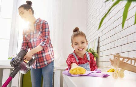 Familia feliz que limpia la habitación. Madre e hija hacen la limpieza de la casa. Una mujer joven y una muchacha del pequeño niño se limpió el polvo y aspirar el suelo. Foto de archivo