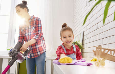 house cleaning: Happy family cleans the room. Mother and daughter do the cleaning in the house. A young woman and a little child girl wiped the dust and vacuumed the floor.