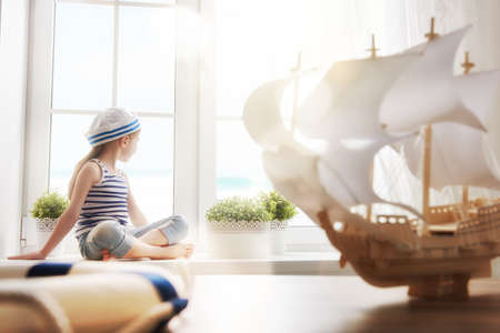 Adorable little child girl sitting on the window. Girl looks at the blue sky and dreams of sea, adventures and travel. Girl has a toy ship.