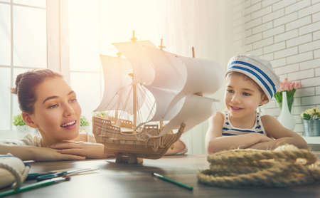 ship captain: Mother and her child girl making model ship. Dreams of sea, adventures and travel. Stock Photo