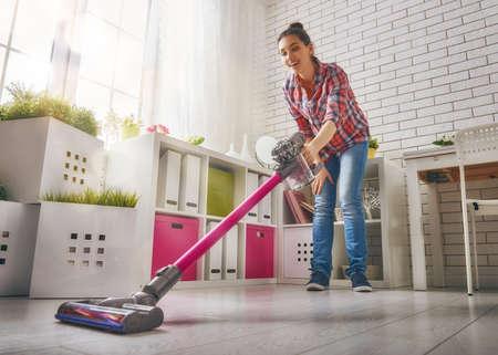 아름 다운 젊은 여자 집 청소합니다. 여자가 바닥을 진공 청소