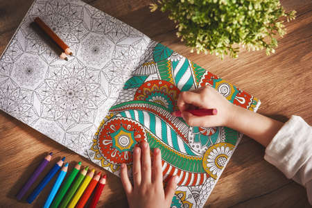 Child paint a coloring book. New stress relieving trend. Concept mindfulness, relaxation. Фото со стока