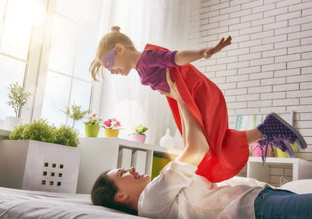 Mother and her child girl playing together. Girl in an costume. The child having fun and jumping on the bed. 스톡 콘텐츠