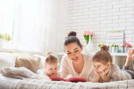 Jolie jeune mère lisant un livre à ses filles Banque d'images - 53230860