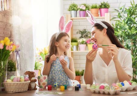 alegria: ¡Felices Pascuas! Una madre y su hija que pintan los huevos de Pascua. la familia feliz que se prepara para la Pascua. niña niño lindo con orejas de conejo en el día de Pascua.