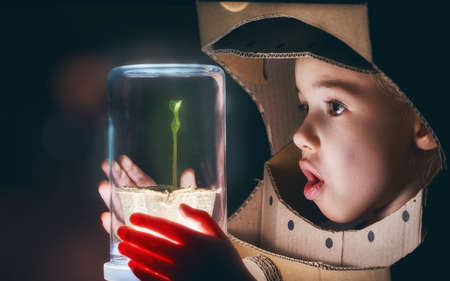 Child is dressed in an astronaut costume. Child sees a sprout in a glass case. The concept of environmental protection.