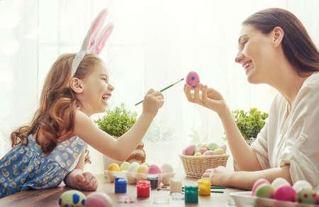 osterhase: Frohe Ostern! Eine Mutter und ihre Tochter Bemalen von Ostereiern. Glückliche Familie für Ostern vorbereitet. Nettes kleines Kind Mädchen mit Hasenohren auf Ostern Tag. Lizenzfreie Bilder