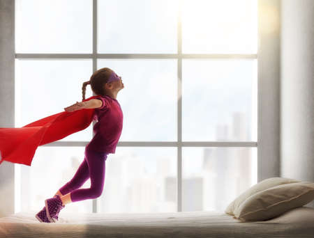 super powers: Child girl in an  costume plays. The child having fun and jumping on the bed. Stock Photo