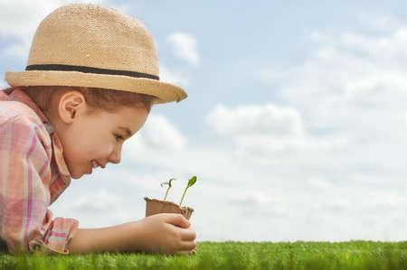 pequeñas plantas de semillero de plantación muchacha del niño lindo. pequeño jardinero divertido. Concepto de primavera, la naturaleza y el cuidado.