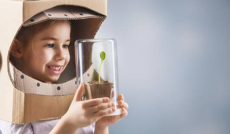 environmental: Child is dressed in an astronaut costume. Child sees a sprout in a glass case. The concept of environmental protection.