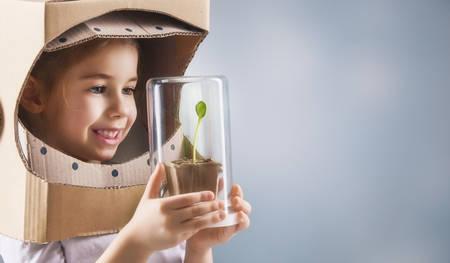 universum: Kind ist in einem Astronauten-Kostüm gekleidet. Kind sieht einen Sprössling in einem Glaskasten. Das Konzept des Umweltschutzes. Lizenzfreie Bilder