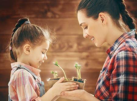 Nettes Kind Mädchen hilft ihrer Mutter für die Pflanzen zu kümmern. Glückliche Familie in der Gartenarbeit im Garten beschäftigt. Mutter und ihre Tochter sehen, wie eine wachsende Spross. Frühling Konzept, Natur und Pflege.