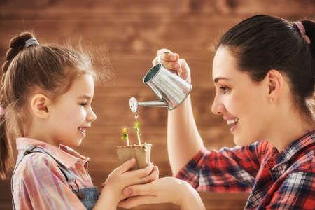 Cute child girl helps her mother to care for plants. Happy family engaged in gardening in the backyard. Mother and her daughter watering a growing sprout. Spring concept, nature and care. Stockfoto