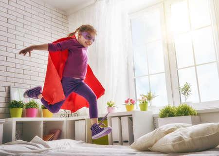 meisje van het kind in een kostuum toneelstukken. Het kind plezier en springen op het bed. Stockfoto
