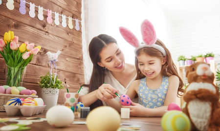 Happy easter! A mother and her daughter painting Easter eggs. Happy family preparing for Easter. Cute little child girl wearing bunny ears on Easter day.