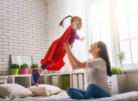 fun: Mother and her child girl playing together. Girl in an  costume. The child having fun and jumping on the bed.