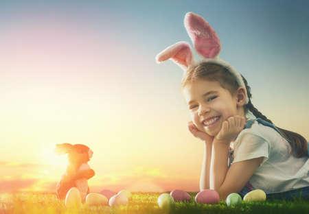 Cute petite fille de l'enfant portant des oreilles de lapin le jour de Pâques. Fille chasse aux ?ufs de Pâques sur la pelouse. Fille avec des oeufs de Pâques et de lapin dans les rayons du soleil couchant. Banque d'images - 53480431
