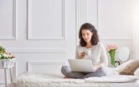 Felice bella donna casual che lavora su un computer portatile seduto sul letto in casa. Archivio Fotografico