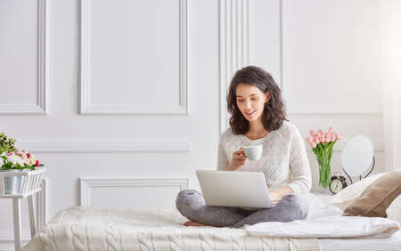 Happy casual beautiful woman working on a laptop sitting on the bed in the house. Stock Photo - 54018480