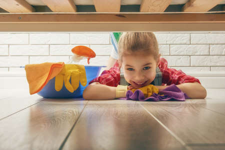 charming girl: Charming little helper. Cute little child girl makes cleaning the house. Girl wipes the floor.