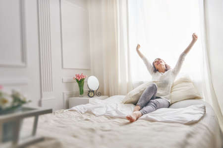 Happy young woman enjoying sunny morning on the bed Imagens - 54018505