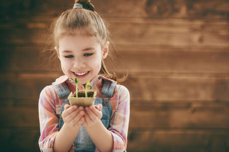 seedling: Cute little child girl planting seedlings. Fun little gardener. Spring concept, nature and care. Stock Photo