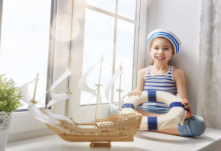 lifeline: Adorable little child girl sitting on the window and holding lifeline. Girl looks at the blue sky and dreams of sea, adventures and travel. Girl has a toy ship.
