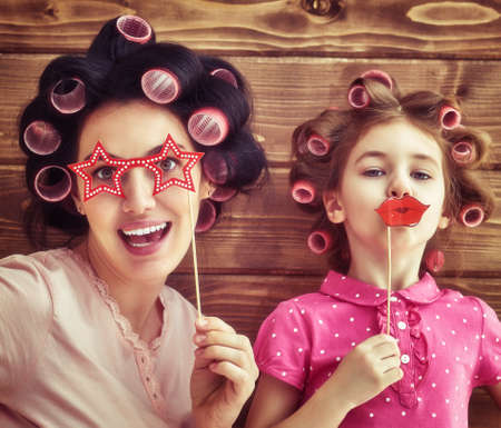 Família engraçada! Matriz e sua menina criança filha com acessórios de papel. Beleza menina engraçada segurando os lábios de papel na vara. Bela jovem segurando copos de papel na vara.