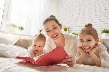 kid reading: happy loving family. pretty young mother reading a book to her daughters