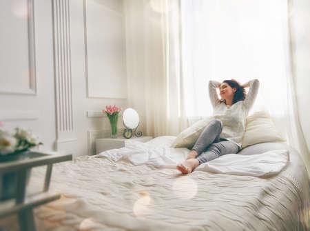 침대에 화창한 아침을 즐기는 행복 한 젊은 여자 스톡 콘텐츠