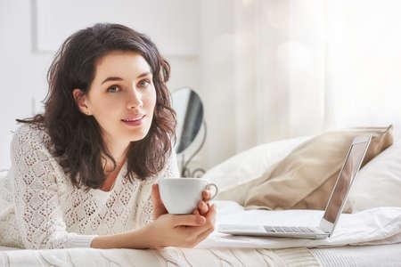 Gelukkig casual mooie vrouw die werkt op een laptop zittend op het bed in het huis.