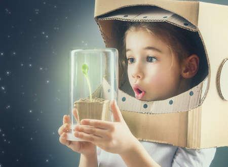 Kind ist in einem Astronauten-Kostüm gekleidet. Kind sieht einen Sprössling in einem Glaskasten. Das Konzept des Umweltschutzes.