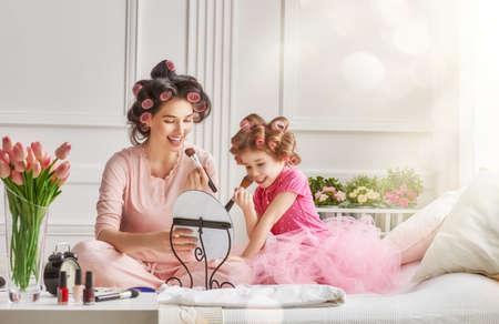 Bonne famille aimante. Mère et fille sont en train de faire les cheveux et avoir du plaisir. Mère et fille faisant votre maquillage assis sur le lit dans la chambre. Banque d'images - 54018528